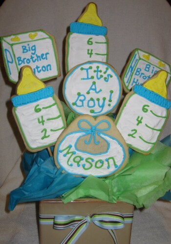 Seven Baby-Themed Sugar Cookies Sticking Out of a Square Bowl with a Bow on It