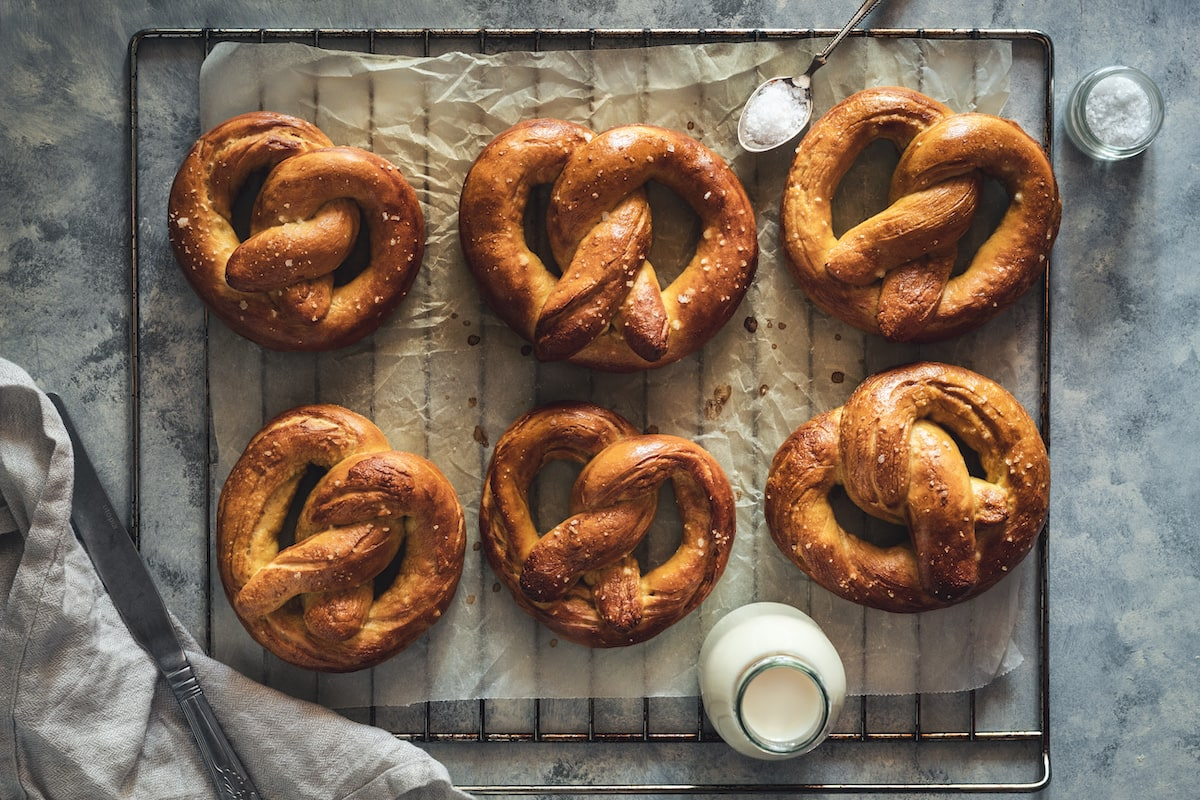 6 homemade soft pretzels on a cooling rack.