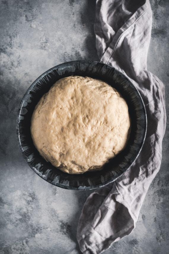 Risen homemade pretzel dough in a bowl.