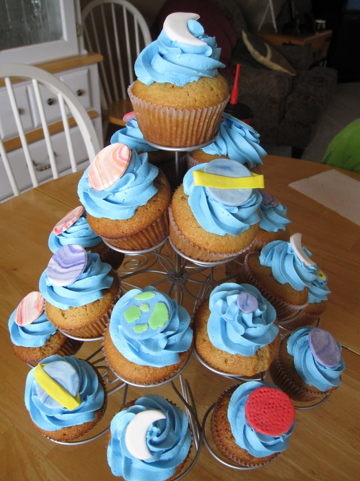 A variety of blue frosted space-themed cupcakes in a cupcake tower