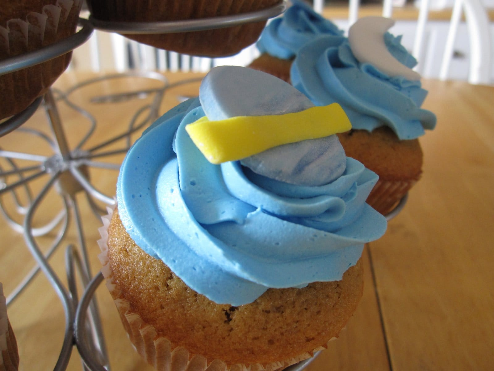 Close-up of a blue frosted cupcake with the planet Saturn on top