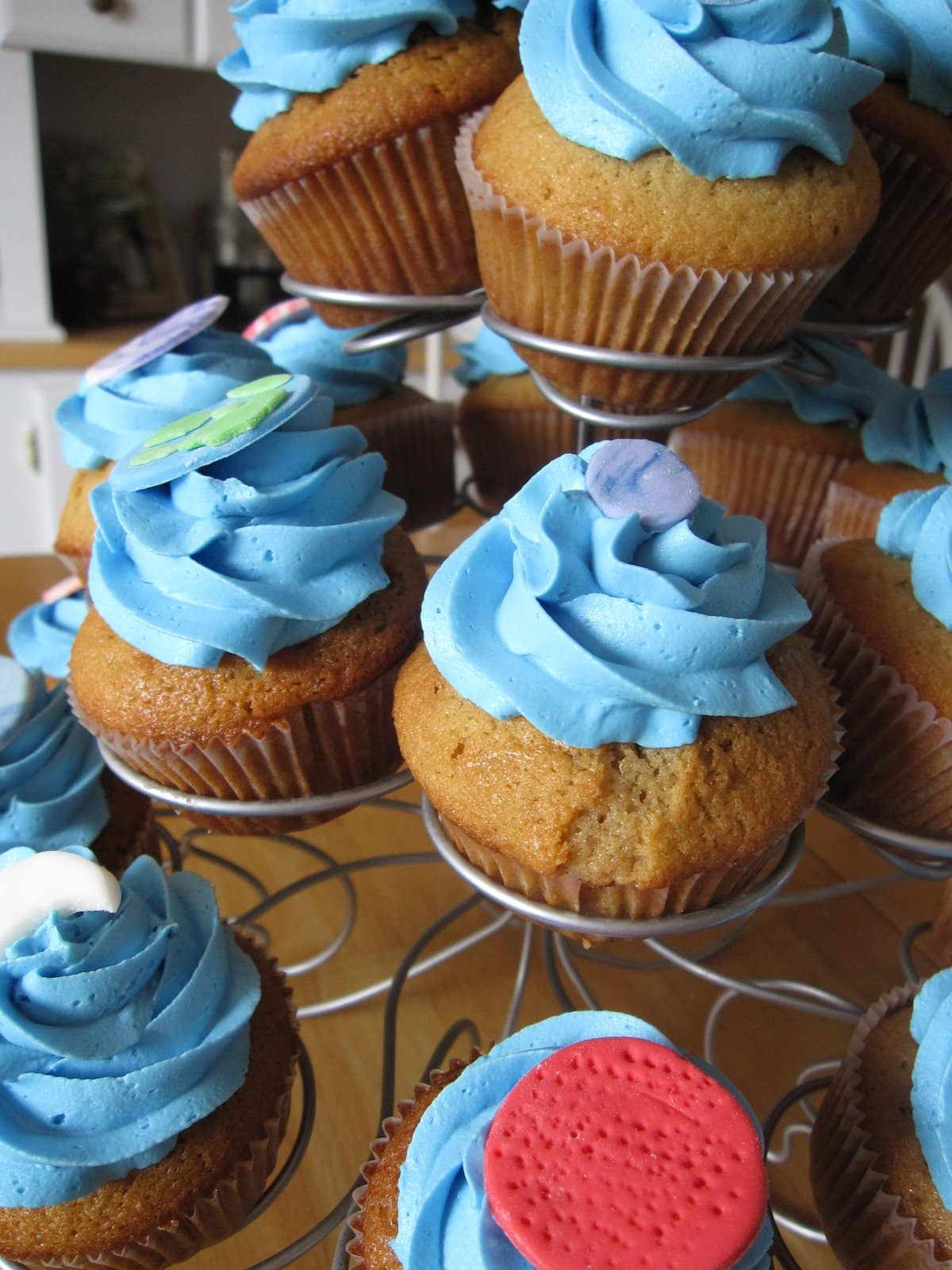 Several blue frosted cupcakes with planet decorations