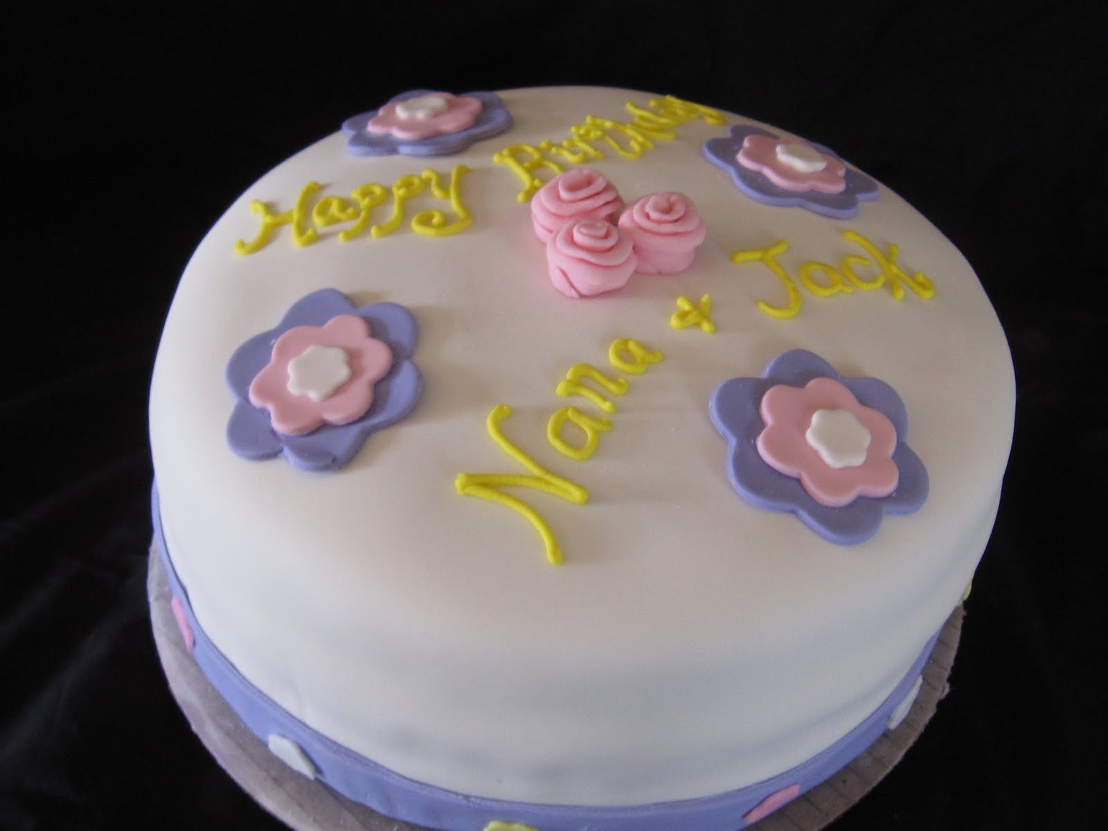 Carrot Cake Decorated with White Fondant, Pink and Purple Flowers, and Yellow Happy Birthday Icing