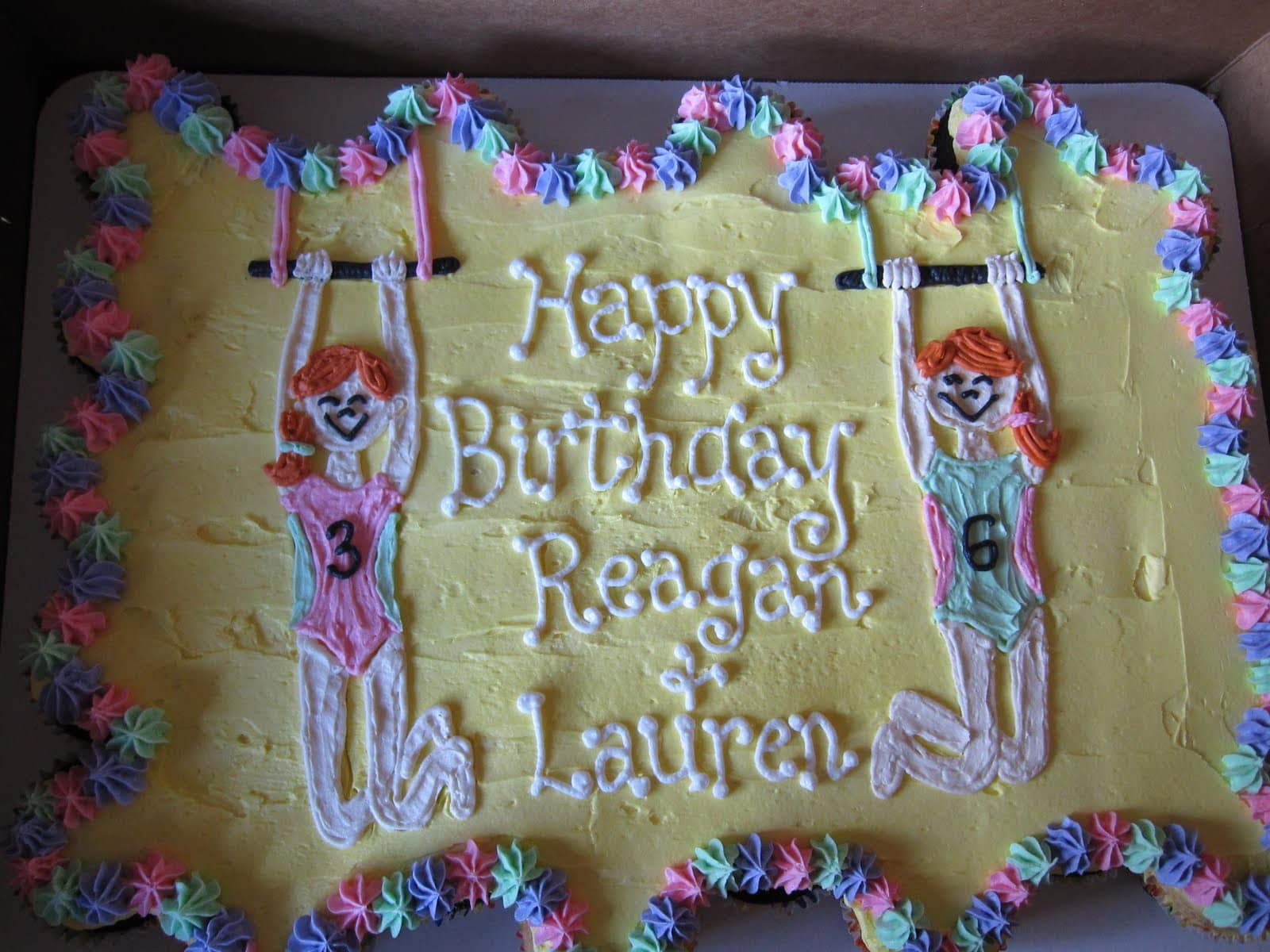 Sheet cake decorated with gymnastics them and Happy Birthday Reagan & Lauren