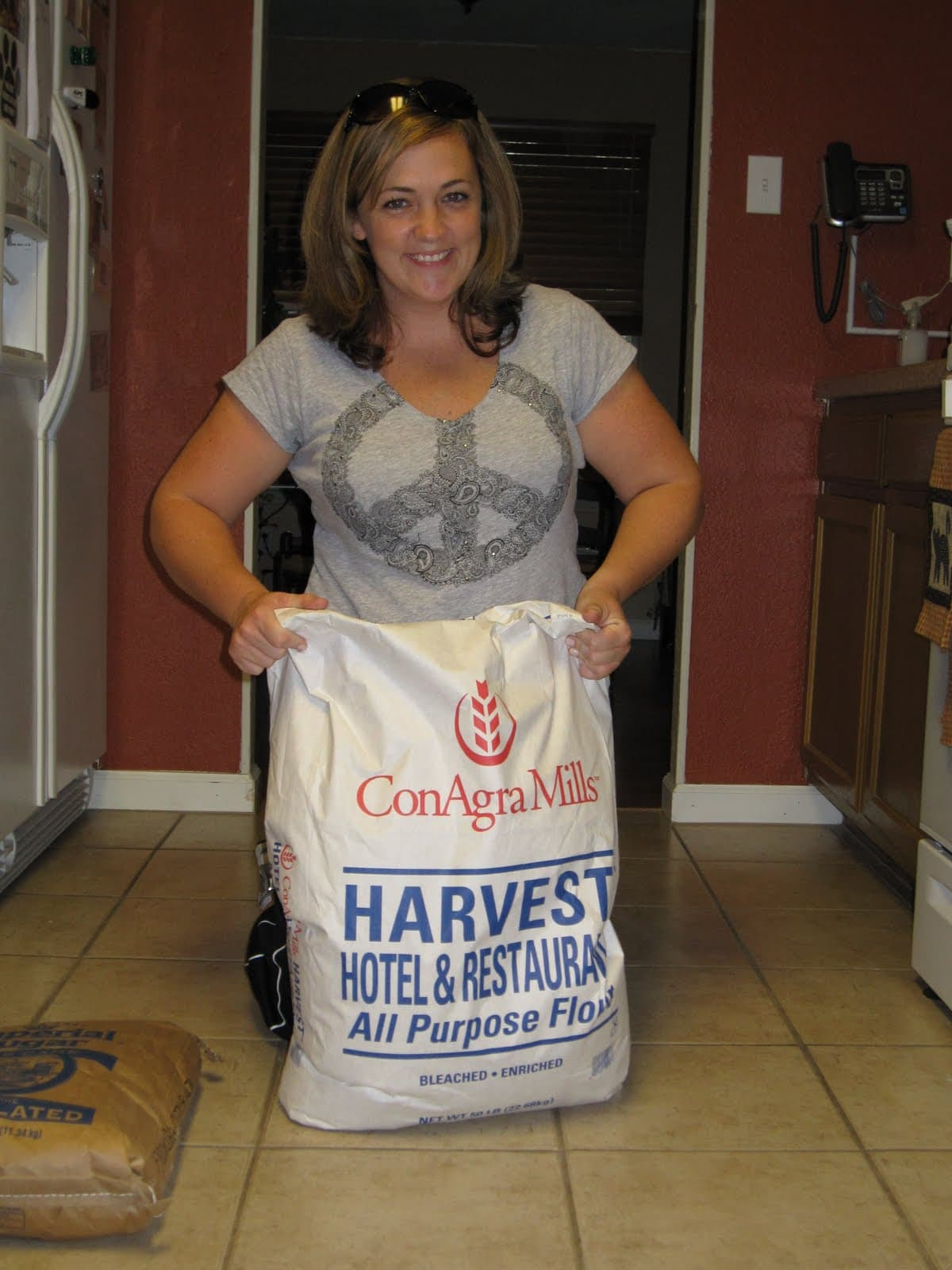 A woman holding up a 50-lb sack of flour