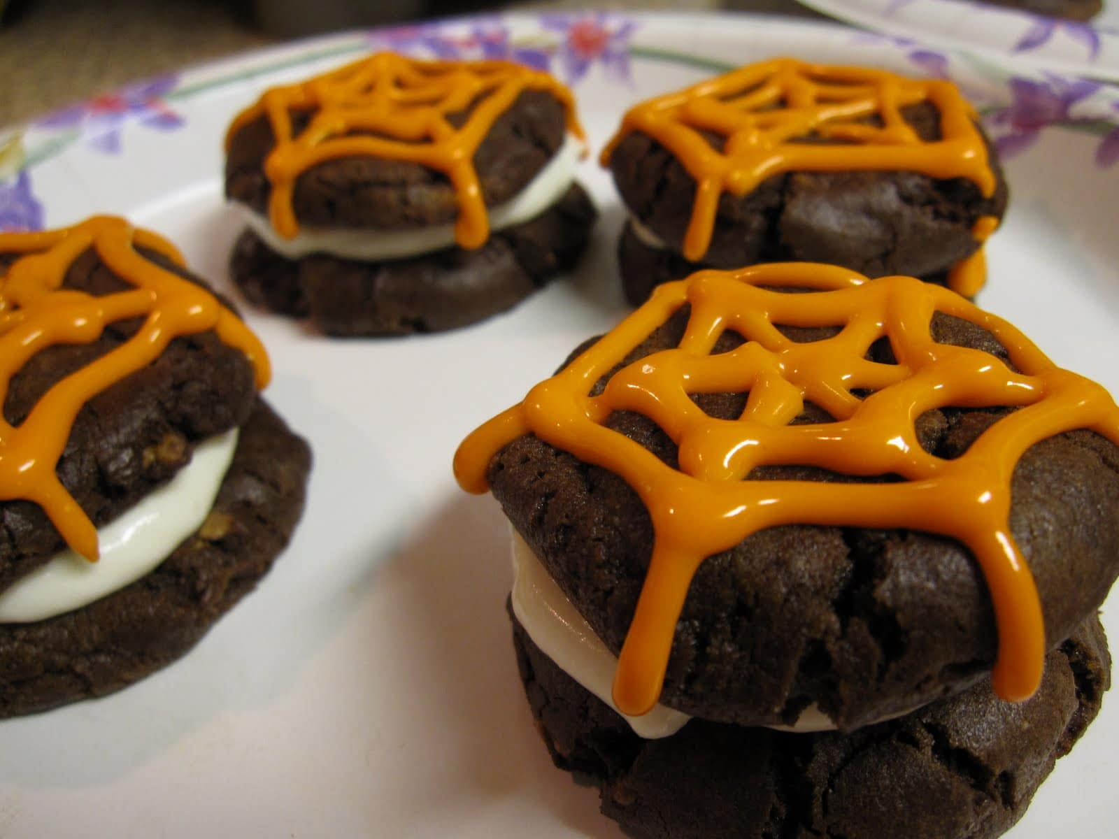 Whoopie pies decorated with orange spiderweb frosting