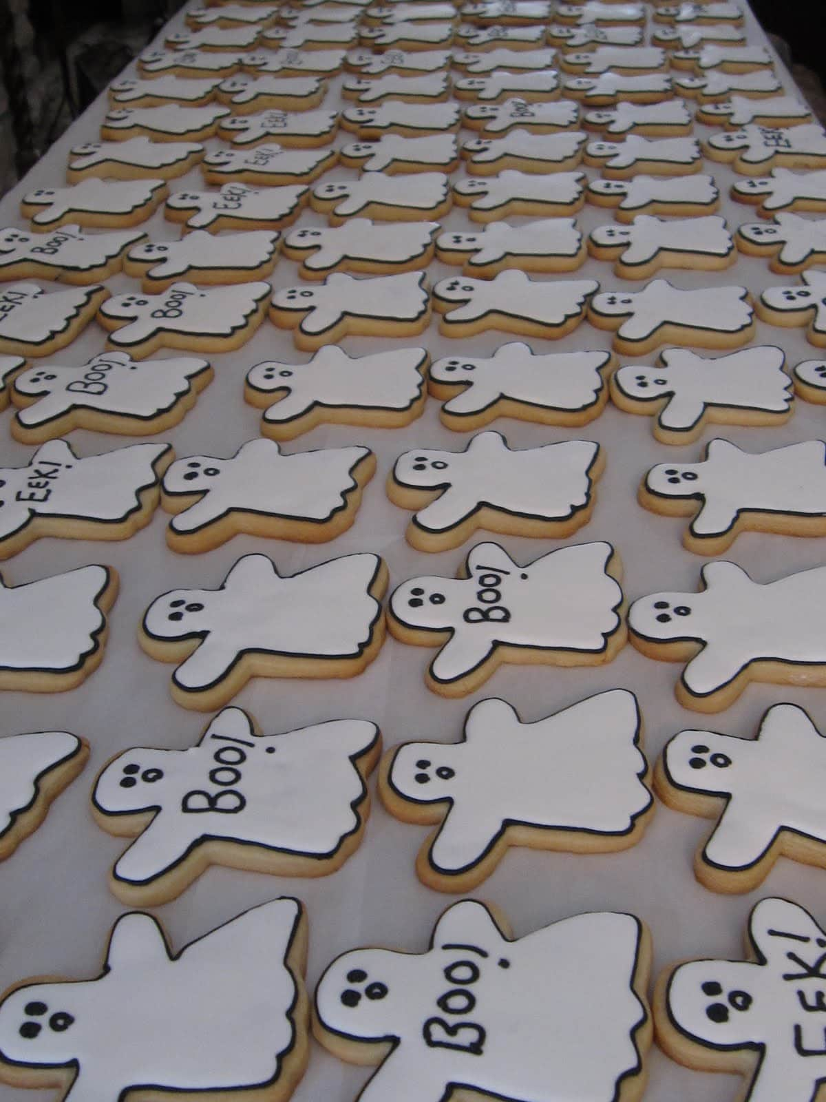 Dozens of ghost frosted cookies on parchment paper