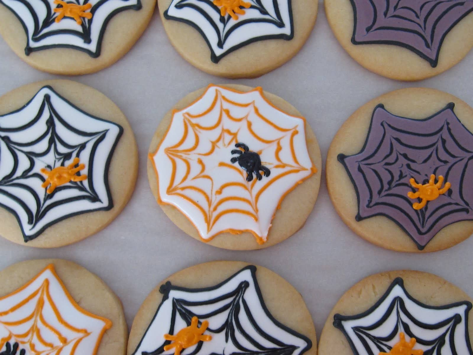 Overhead view of several spiderweb decorated frosted cookies