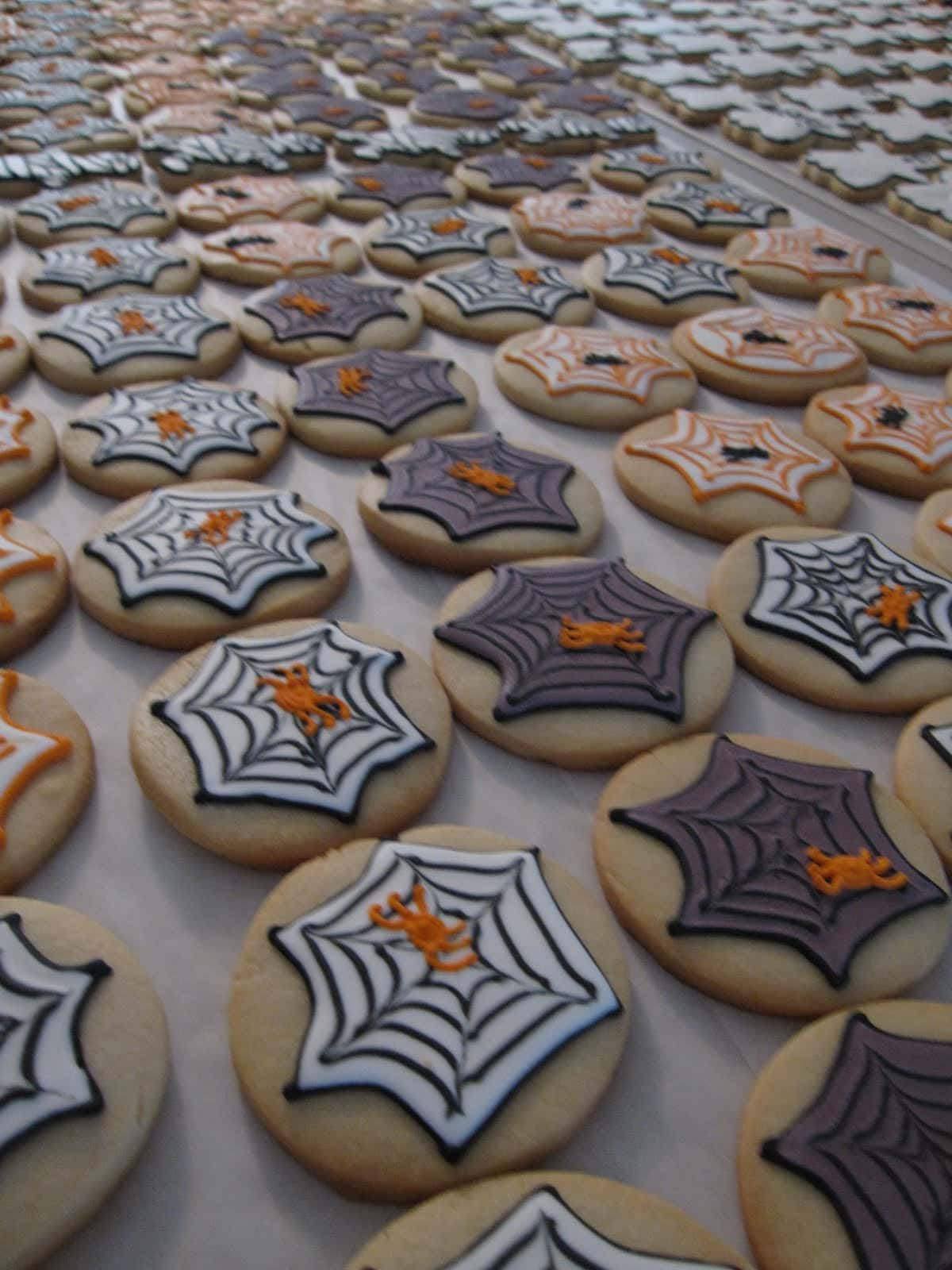 A variety of spiderweb-decorated frosted cookies