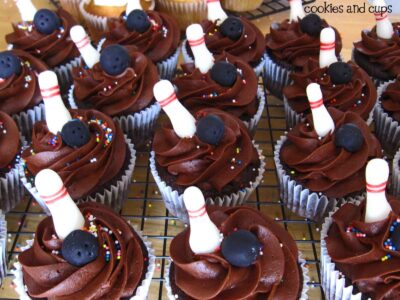Close-up of chocolate cupcakes with bowling pin decorations