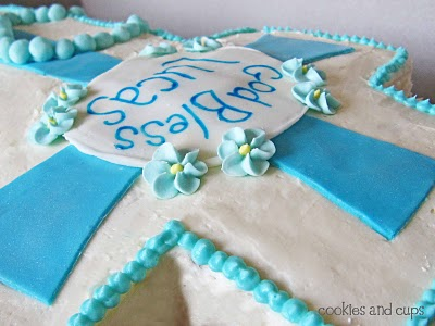"""A Close-Up Shot of a Cross Cake with """"God Bless"""" Written on Fondant"""