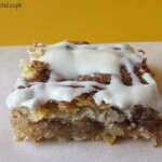 A Cinnamon Toast Crunch Apple Pie Bar Covered in Homemade Glaze on a White Surface