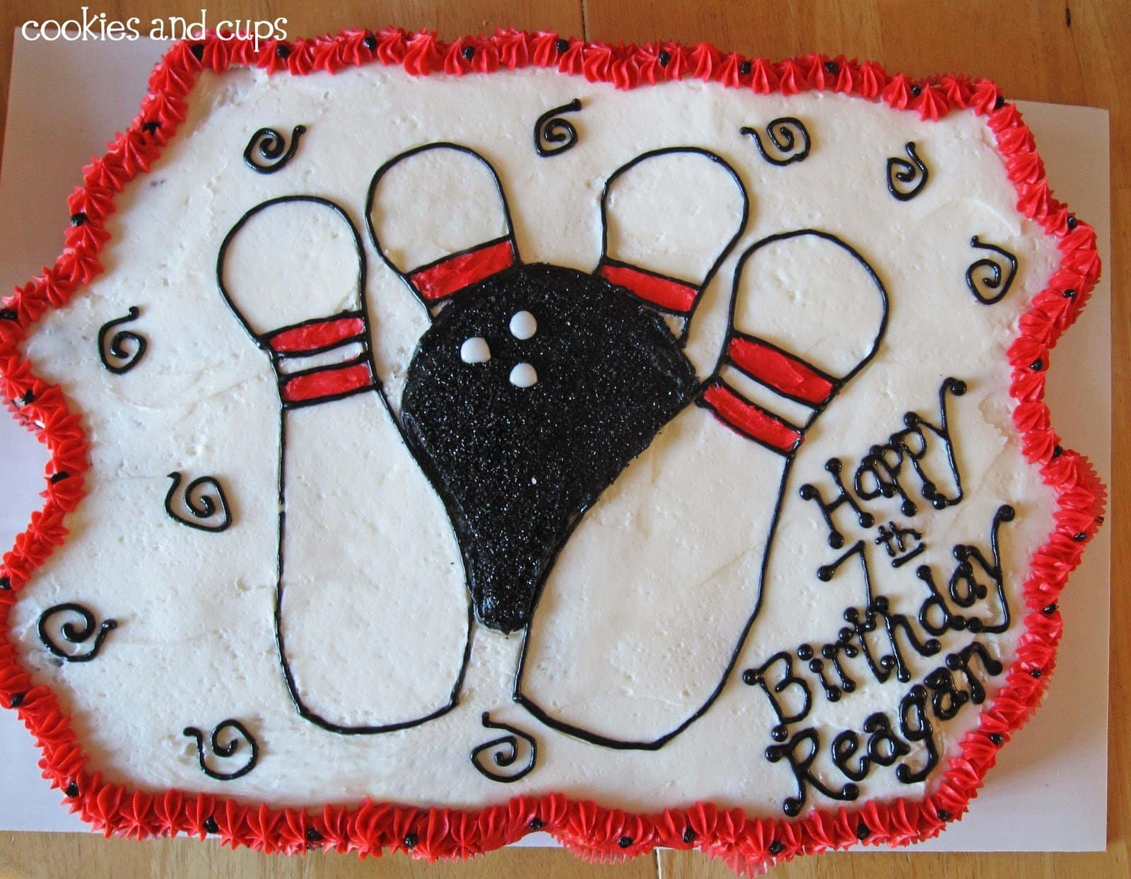 Top view of a cake decorated with bowling pins and a bowling ball