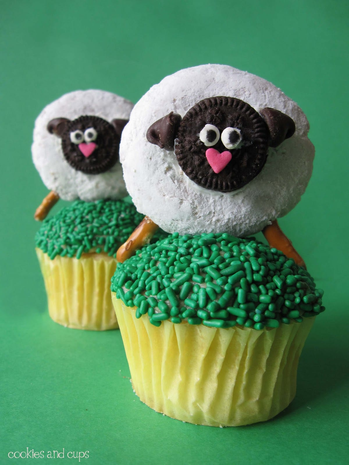 Two Sheep Cupcake Toppers on Top of Two Cupcakes with Green Frosting and Green Sprinkles