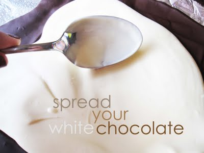 A Spoon Spreading Melted White Chocolate Over Set Dark Chocolate in a Foil-Lined Pan