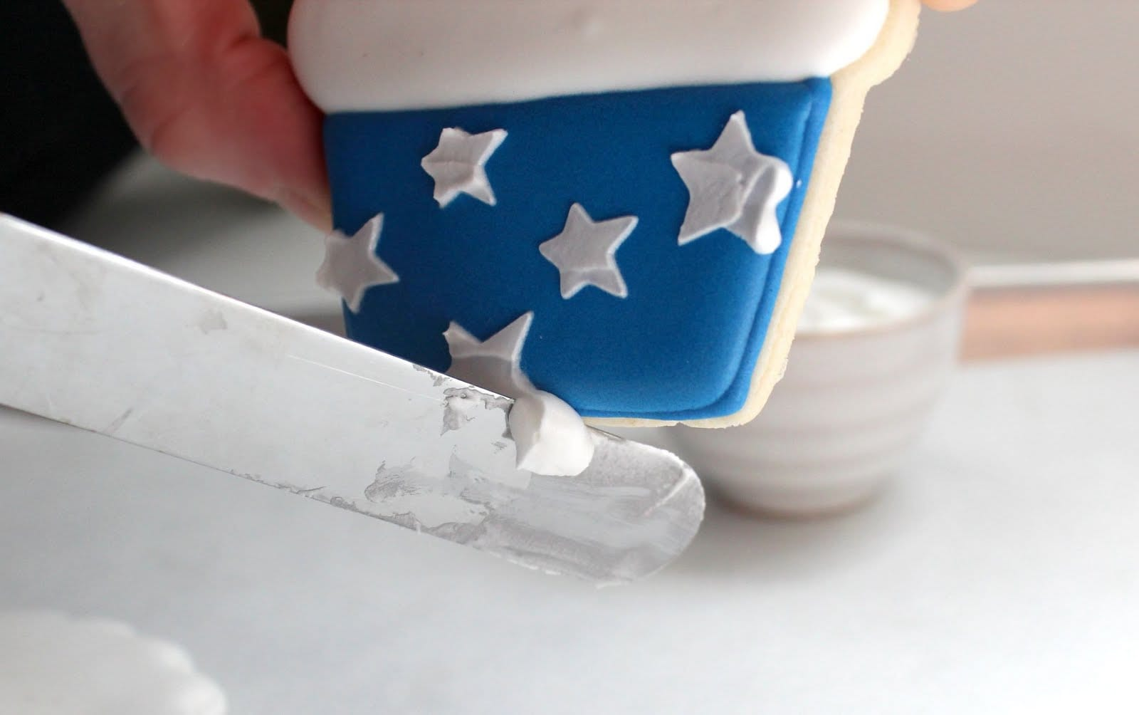 A knife removing extra frosting from a cupcake-shaped cookie