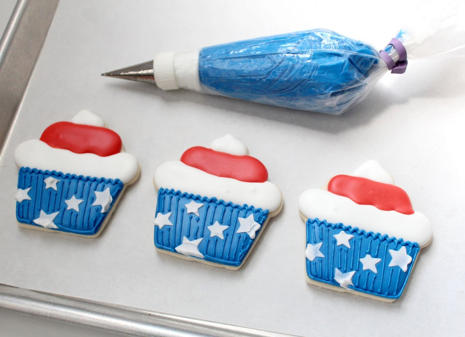Blue frosting in a piping bag with 3 stars and stripes cupcake cookies
