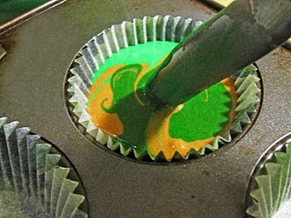 Swirling camo cupcake batter colors together in a muffin tin