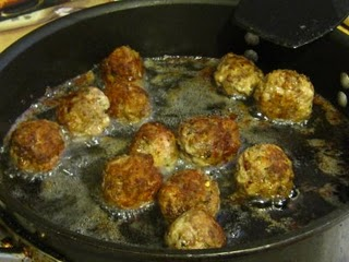 Meatballs frying in a skillet