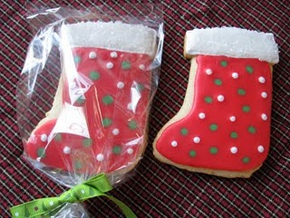 Two Red Polka Dot Stocking Decorated Christmas Cookies on a Red and Green Tablecloth