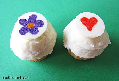 Two vanilla frosted cupcakes decorated with a red heart and a purple flower