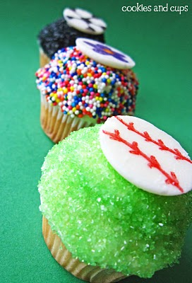 A baseball, flower and soccer ball cupcake arranged in a line