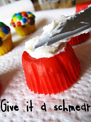 Frosting being spread on an inverted red muffin cup