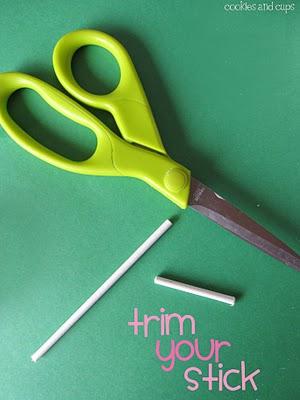 A Pair of Green Scissors Beside a Trimmed Lolipop Stick