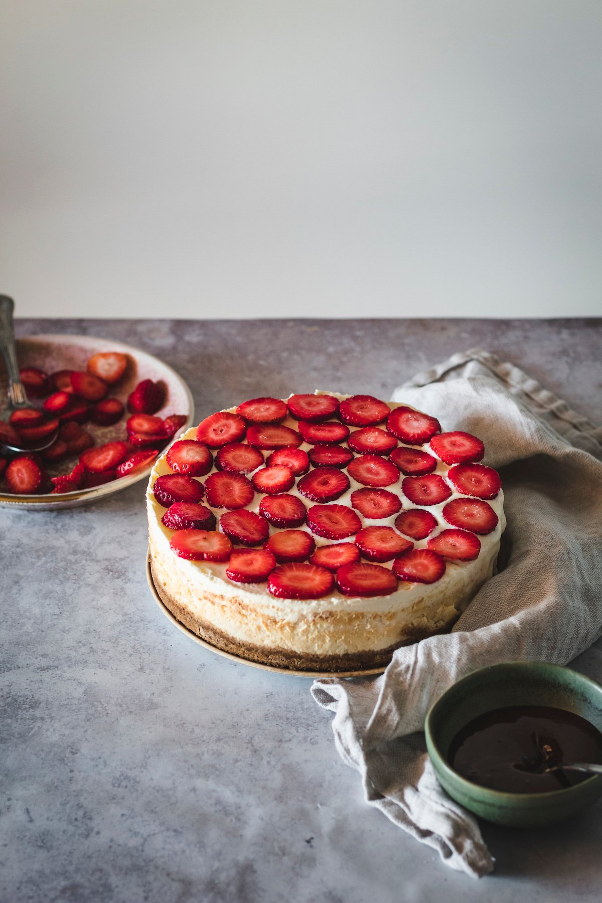 Sliced strawberries on top of a cheesecake.