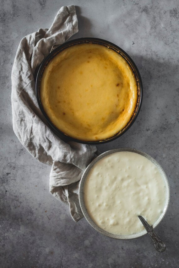 Baked cheesecake next to a bowl of vanilla mousse.