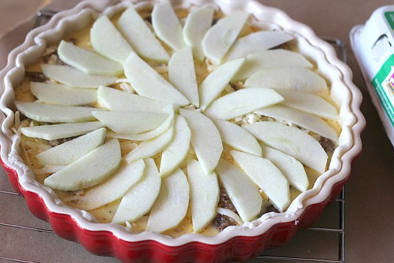 Apple slices decoratively arranged on top of Egg, Sausage, Apple and cheese tart
