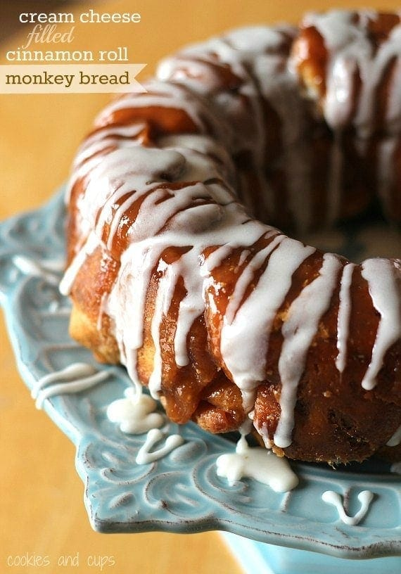 Title image of Cinnamon Roll Monkey Bread with Cream Cheese Filling drizzled with vanilla icing.