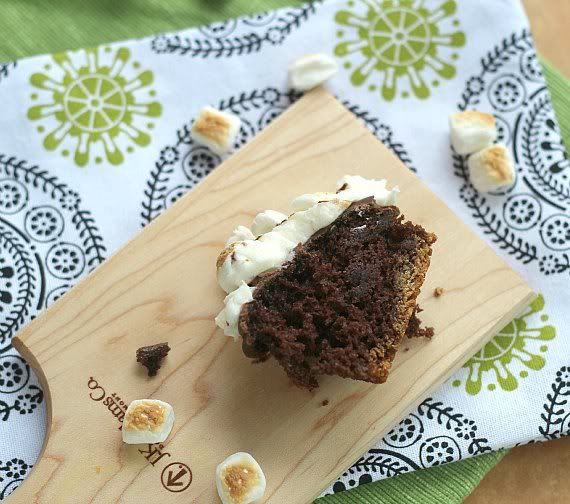 Half of a S'mores cupcake on a wooden cutting board