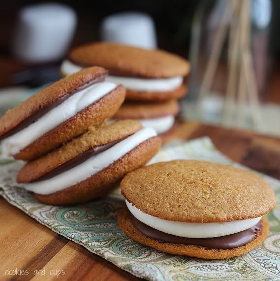 Several S'mores Whoopie Pies with chocolate and marshmallow filling on a tea towel