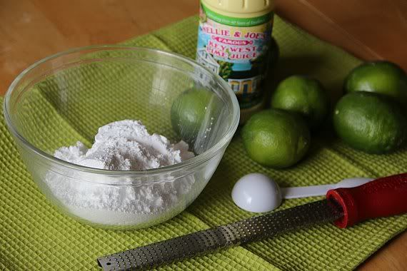 A bowl of powdered sugar and several limes