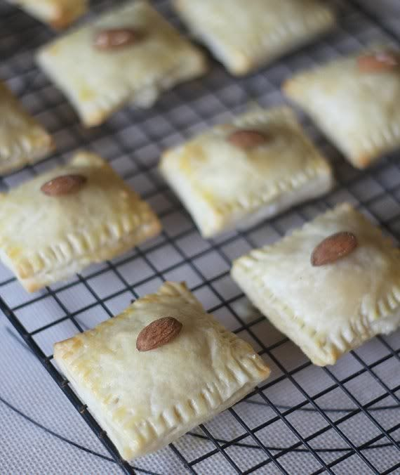 Pastry squares topped with an almond on a cooling rack