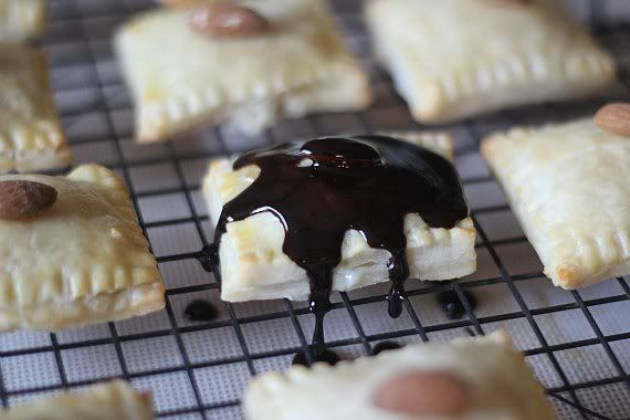 Pastry square covered in melted chocolate on a cooling rack