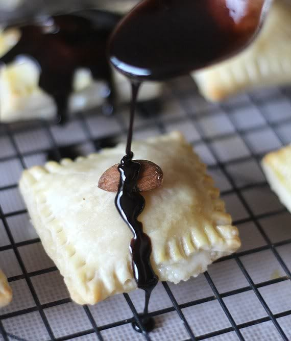 Chocolate being drizzled over pastry squares on a cooling rack