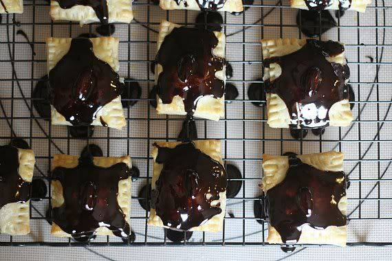 Pastry squares drizzled with melted chocolate on a cooling rack