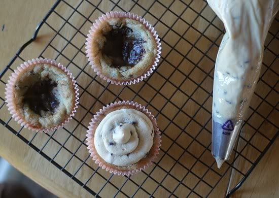 Top view of cookie cups on a cooling rack and one complete with cookie dough filling