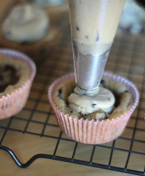 Cookie dough being piped into a baked cookie cup