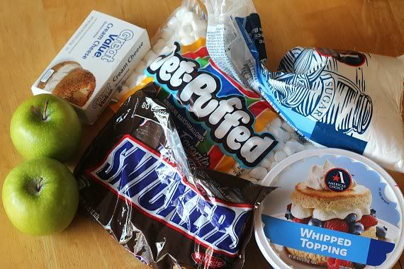 Ingredients for Snickers salad, including marshmallows, whipped topping, cream cheese and Snickers candy