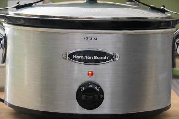 Side view of a stainless steel slow cooker