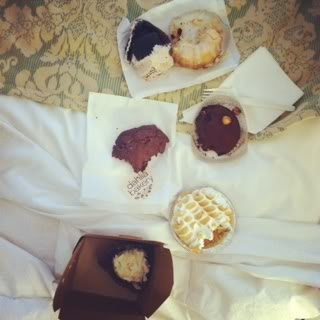 Top view of a variety of bakery treats on a hotel bed