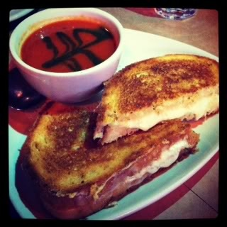 Grilled cheese on a plate with a cup of tomato soup