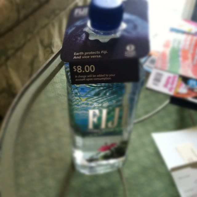 A bottle of Fiji water with an $8.00 price tag