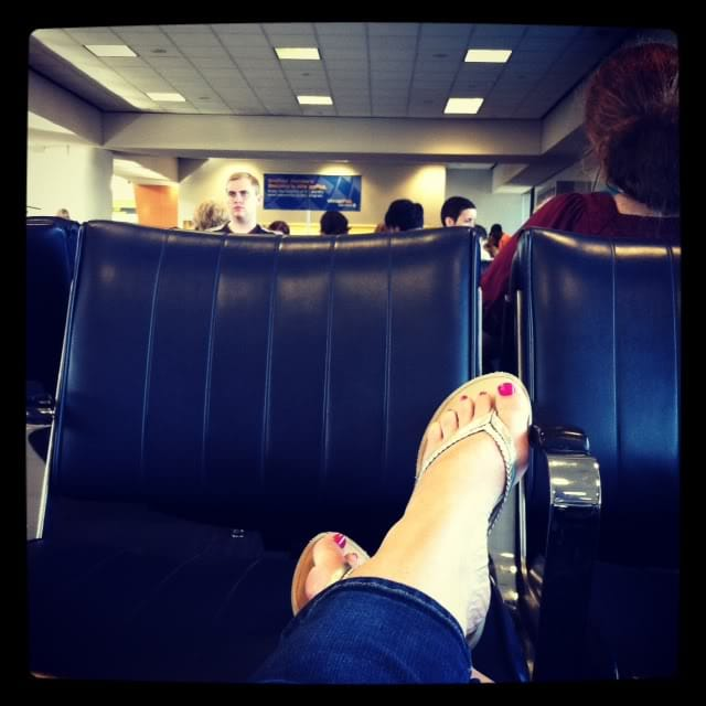 A woman's feet resting on a set of chairs at the airport