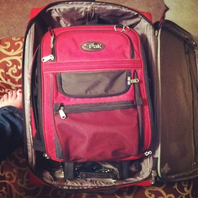 Top view of a red suitcase nested inside another suitcase