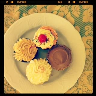 Top view of four different varieties of cupcakes on a plate