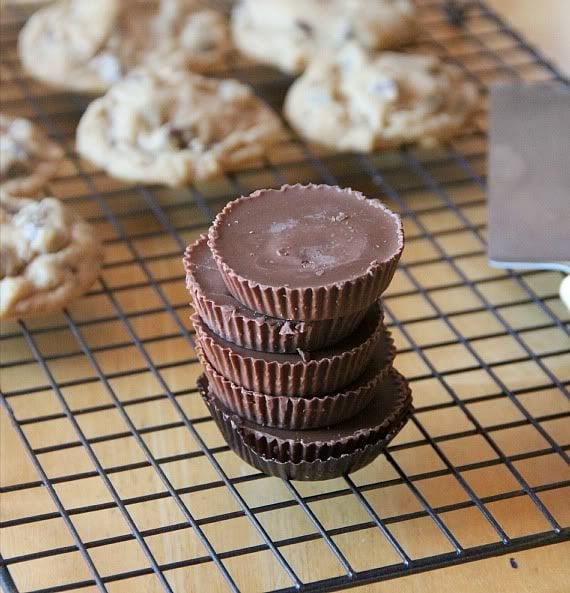 Chocolate chip cookies and a stack of peanut butter cups on a cooling rack